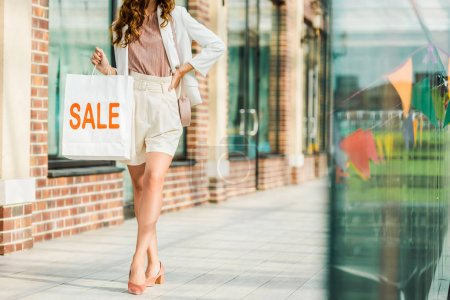 cropped shot of stylish woman holding shopping bag with sale sign at mall