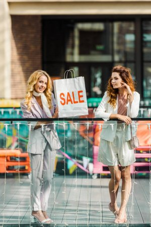 Photo for Fashionable young women spending time together in mall with shopping bag with sale sign - Royalty Free Image