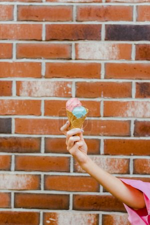 cropped shot of woman holding delicious ice cream in waffle cone in front of brick wall