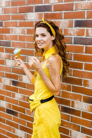 attractive young woman in yellow clothes with ice cream looking at camera in front of brick wall