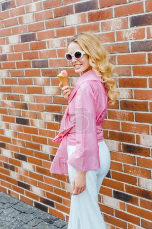 smiling young woman in pink holding ice cream and looking at camera in front of brick wall