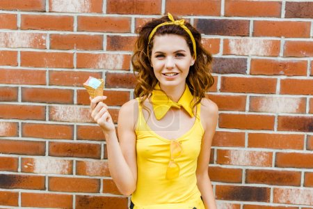 happy young woman in yellow clothes with ice cream looking at camera in front of brick wall