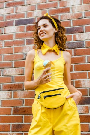 happy young woman in yellow clothes with ice cream posing in front of brick wall