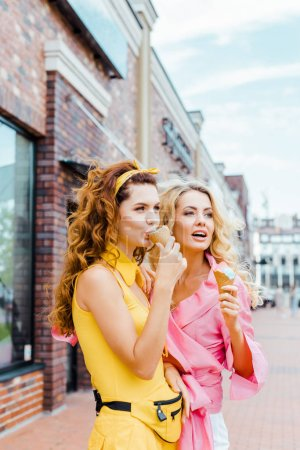 beautiful young women in colorful clothes eating ice cream in waffle cones on street