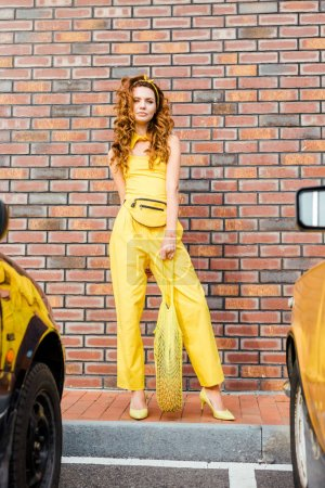 beautiful young woman in yellow clothes with pineapple in string bag standing at parking in front of brick wall