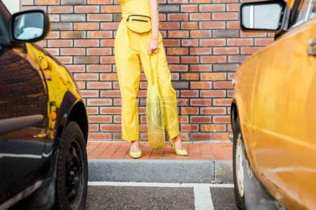 cropped shot of woman in yellow clothes with pineapple in string bag standing at parking in front of brick wall