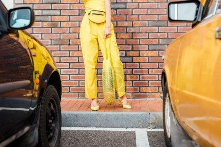 Photo pour Plan recadré de femme en vêtements jaunes avec ananas dans un sac à ficelle debout au parking devant un mur de briques - image libre de droit