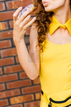 cropped shot of young woman in yellow clothes eating donut in front of brick wall