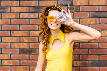 smiling young woman in yellow clothes looking at camera through donut in front of brick wall