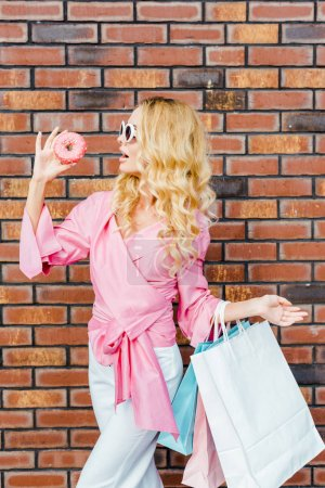 stylish young woman with shopping bags and donut looking at camera in front of brick wall