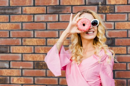 happy young woman in pink shirt looking at camera through donut in front of brick wall