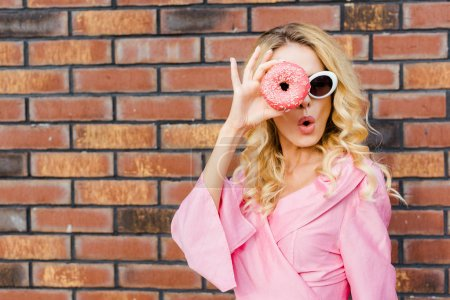 surprised young woman in pink shirt looking at camera through donut in front of brick wall
