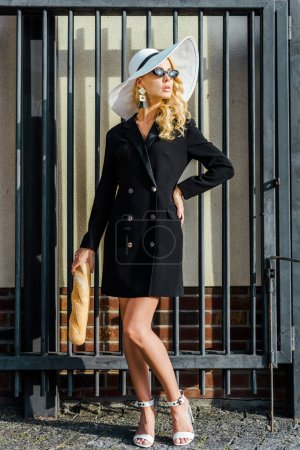 Photo for Beautiful young woman in stylish jacket and hat standing in front of fence with baguette - Royalty Free Image