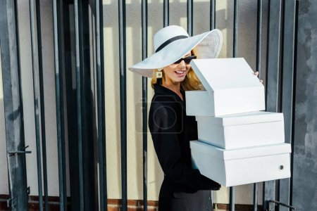 happy young woman in stylish clothes holding stack of white shoe boxes