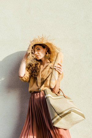 fashionable young woman in straw hat with baguette standing in front of white wall and looking at camera