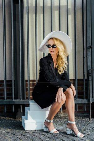 Foto de Moda joven en ropa elegante sentado en cajas de zapatos apiladas en la calle - Imagen libre de derechos