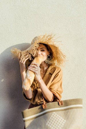 beautiful young woman in straw hat standing in front of white wall an eating baguette