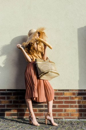 attractive stylish woman in straw hat standing in front of white wall and eating french baguette
