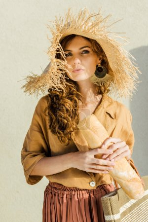 fashionable beautiful woman in straw hat with baguette standing in front of white wall