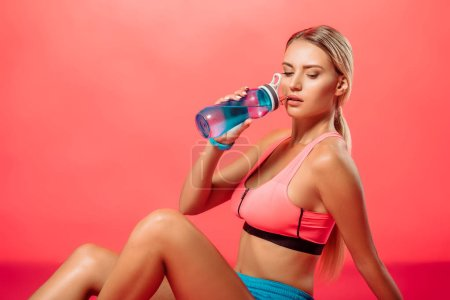 attractive sportswoman drinking water from sport bottle on red