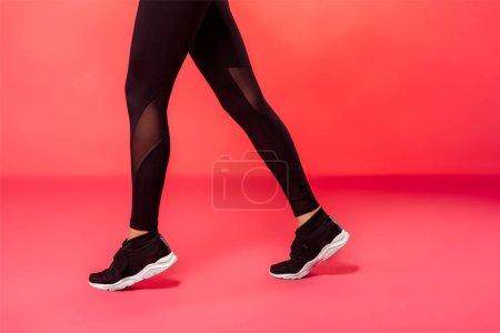 Photo pour Image recadrée de sportive marche en collant noir sur rouge - image libre de droit