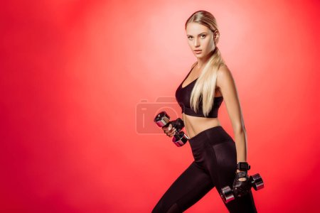 Photo for Attractive sportswoman training with dumbbells isolated on red and looking at camera - Royalty Free Image