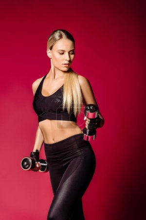 Photo for Attractive sportswoman training with dumbbells isolated on burgundy - Royalty Free Image