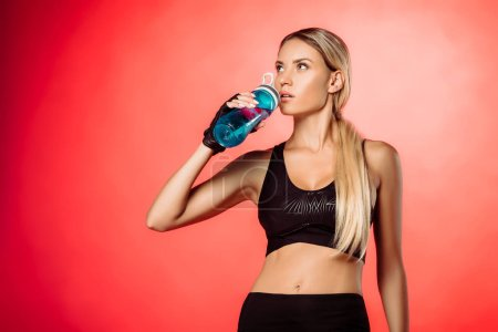 attractive sportswoman drinking water from sport bottle isolated on red