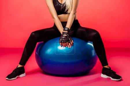 cropped image of sportswoman sitting on blue fitness ball on red
