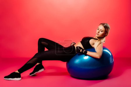 attractive sportswoman exercising on fitness ball on red
