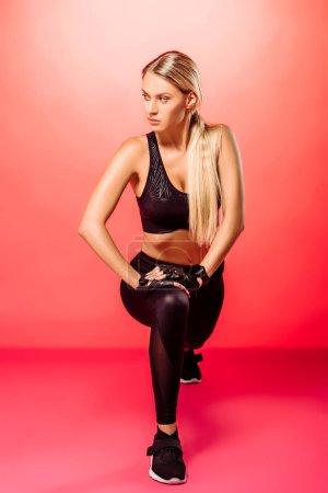 Photo pour Séduisante sportive aux cheveux longs qui s'étend de jambes sur le rouge - image libre de droit