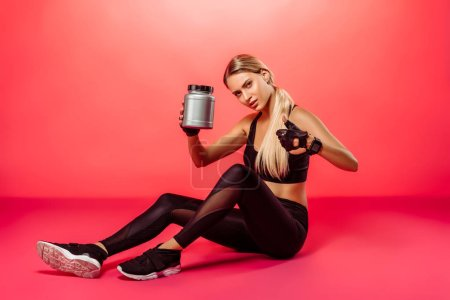 attractive sportswoman sitting with sport supplement jar on red and showing thumb up