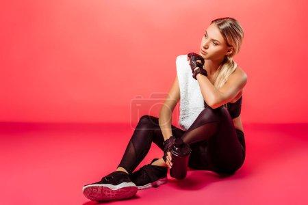 Photo pour Séduisante sportive assis avec serviette et sport bottle avec protéines sur rouge - image libre de droit