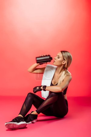 attractive sportswoman sitting with towel and drinking protein supplement from sport bottle on red