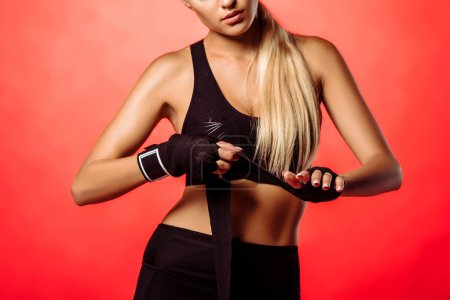 cropped image of sportswoman wearing sport gloves isolated on red