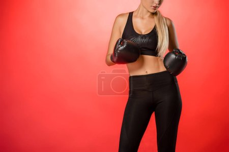 cropped image of female boxer standing with boxing gloves isolated on red