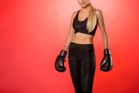 cropped image of boxer standing with boxing gloves isolated on red