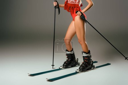 partial view of woman in red swimming suit, scarf with skiing equipment on grey backdrop
