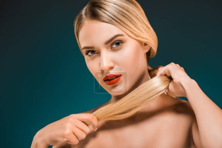 portrait of beautiful young woman with red lips holding hair on dark background
