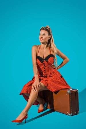 attractive young pin up woman in retro dress sitting on suitcase on blue backdrop
