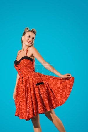 portrait of cheerful pin up woman in retro dress posing isolated on blue