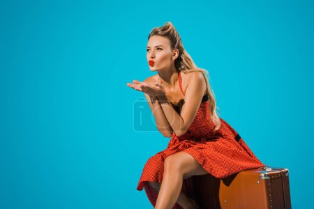 attractive young woman in pin up style dress blowing kiss while sitting on suitcase on blue backdrop