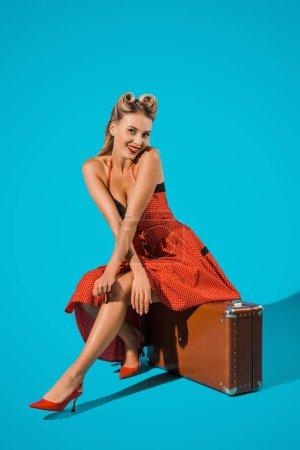 Photo pour Souriant pin up femme en robe rétro assis sur la valise sur fond bleu - image libre de droit