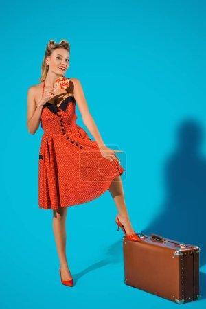 smiling woman in vintage dress with lollipop and suitcase on blue backdrop
