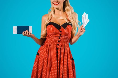 cropped shot of smiling woman in retro dress with paper plane, ticket and passport isolated on blue