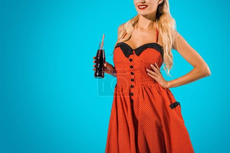 cropped shot of smiling woman in vintage dress with soda drink in glass bottle on blue backdrop