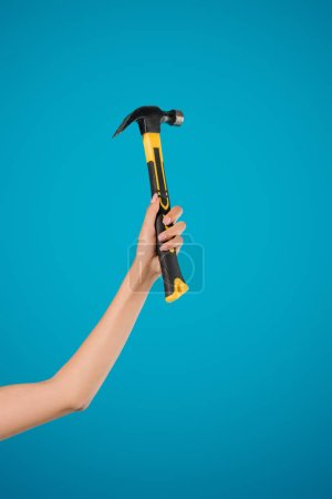 cropped shot of woman holding hammer in hand isolated on blue