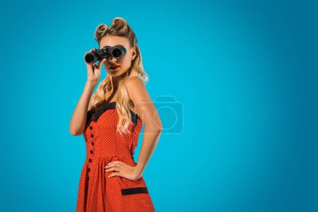 side view of fashionable pin up woman in retro style clothing with binoculars on blue background
