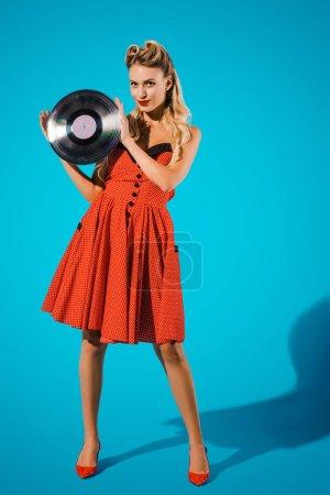 jeune pin up femme en robe vintage élégante avec disque de vinyle sur fond bleu