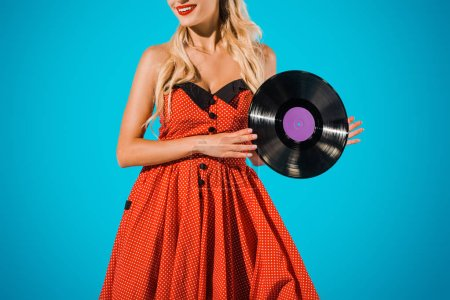 partial view of woman in vintage dress showing vinyl record on blue backdrop